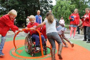 Spelende kinderen, waarvan 1 in een rolstoel