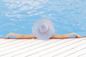 iemand met grote hoed van achteren aan rand van zwembad