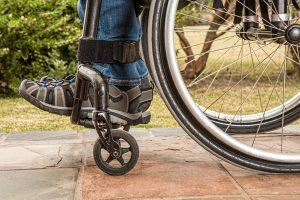 afbeedling voorste wieltjes met voeten op steun van een rolstoel